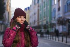 Милая девушка брюнет нося фиолетовые пальто, шляпу и шарф зимы, идя европейской улицей на зиме, обернутой вверх в a Стоковая Фотография RF