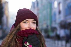 Милая девушка брюнет нося фиолетовые пальто, шляпу и шарф зимы, идя европейской улицей на зиме, обернутой вверх в a Стоковые Фото