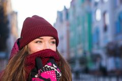 Милая девушка брюнет нося фиолетовые пальто, шляпу и шарф зимы, идя европейской улицей на зиме, обернутой вверх в a Стоковые Фотографии RF