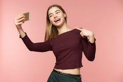 Милая девушка брюнет принимает selfie Она усмехается широко Она имеет длинные волнистые волосы брюнет Девушка красоты на пинке Стоковое Изображение RF