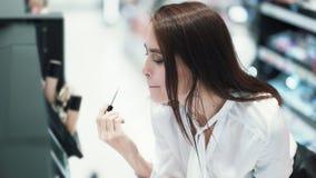 Милая девушка выбирает губную помаду в косметиках ходит по магазинам, пробует ее на губах, замедленное движение акции видеоматериалы