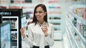 Милая девушка выбирает духи в косметиках ходит по магазинам, распылила ее на тестере и вдохах сток-видео