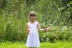 Милая девушка в белом платье играет с пузырями мыла Стоковая Фотография