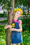 Милая девушка в венке одуванчиков держа букет одуванчиков в ее стойках руки обнимая ствол дерева стоковая фотография