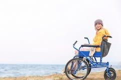 Милая девушка в кресло-коляске на море стоковые изображения