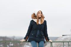 Милая девушка в крышке и куртке зимы сидя на перилах переплюните Стоковые Изображения RF
