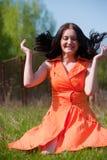 Милая девушка в оранжевом платье на траве Стоковое фото RF