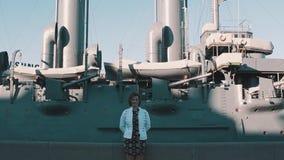 Милая девушка в платье лета стоя перед старым музеем линкора видеоматериал