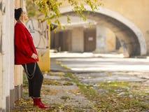 Милая девушка в связанной куртке шляпы красной и красных ботинках стоя около роста стены полностью в на открытом воздухе стоковая фотография rf