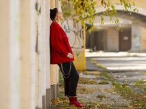 Милая девушка в связанной куртке шляпы красной и красных ботинках стоя около роста стены полностью в на открытом воздухе стоковые изображения rf