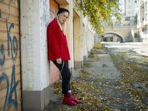 Милая девушка в связанной куртке шляпы красной и красных ботинках стоя около роста стены полностью в на открытом воздухе стоковое фото