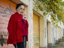 Милая девушка в связанной куртке шляпы красной и красных ботинках стоя около стены в на открытом воздухе стоковые изображения