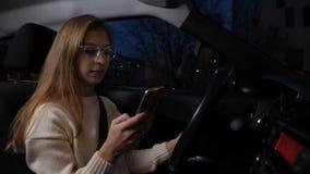Милая девушка в стеклах управляет в вечере, смотря телефон, чтение, печатая сообщению 4K медленный Mo видеоматериал