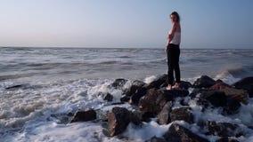 Милая девушка в футболке стоит на утесах в море, вокруг волн, брызгая видеоматериал