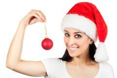 Милая девушка в шлеме Santa Claus с шариком рождества Стоковые Изображения RF