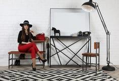 Милая девушка в шляпе сидя на стенде в студии стоковое изображение