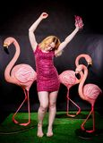 Милая девушка в sequins фуксии одевает отдыхать и танцевать с 3 большими фламинго на черной предпосылке стоковые изображения