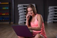 Милая девушка говоря на телефоне после разминки Спортсмен с компьтер-книжкой на запачканной предпосылке Активная принципиальная с Стоковая Фотография RF