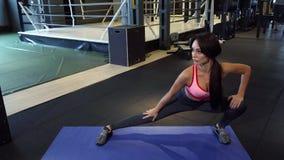 Милая девушка делает тренировки подогрева для ног стоя на циновке видеоматериал