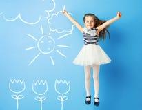 Милая девушка делая чертежи на стене стоковая фотография