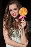 Милая девушка ест конфету леденца на палочке конфеты сладкую стоковые фотографии rf