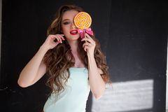 Милая девушка ест конфету леденца на палочке конфеты сладкую стоковое фото rf