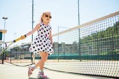 Милая девушка играя теннис и представляя для камеры Стоковое Изображение