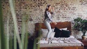 Милая девушка имеет танцы потехи на кровати дома слушая к музыке при наушники скача и поднимая руки самомоднейше видеоматериал