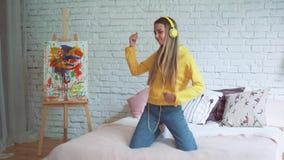 Милая девушка имеет танцы потехи на кровати дома слушая к музыке при наушники скача и поднимая руки самомоднейше сток-видео