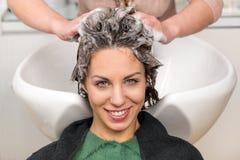 Милая девушка имея ее волосы быть помытым в салоне стоковые фотографии rf