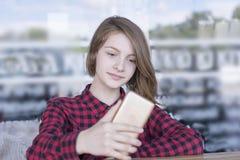 Милая девушка используя телефон outdoors стоковые изображения rf