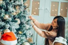 Милая девушка и ее мать украшая ель на Рожденственской ночи Стоковое фото RF