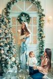 Милая девушка и ее мать украшая ель на Рожденственской ночи Стоковое Фото