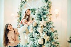 Милая девушка и ее мать украшая ель на Рожденственской ночи Стоковые Изображения RF