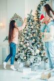 Милая девушка и ее мать украшая ель на Рожденственской ночи Стоковая Фотография RF