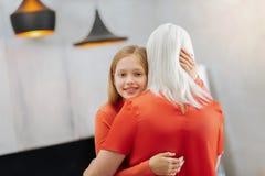 Милая милая девушка касаясь ее голове бабушек Стоковое фото RF