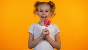Милая девушка конфеты лижа очень вкусный в форме сердц леденец на палочке и усмехаясь, счастье видеоматериал
