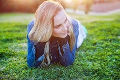 Милая девушка лежа вниз на зеленой траве Стоковое фото RF