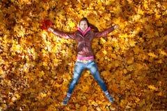 Милая девушка лежит в желтых листьях Стоковые Фотографии RF