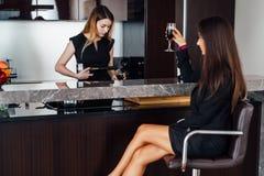 Милая девушка лить красное вино в стекле пока ее женский друг ждать ее для того чтобы сказать здравицу сидя в кухне Стоковые Изображения RF