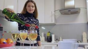 Милая девушка льет шампанское в стекла на кухне дома акции видеоматериалы