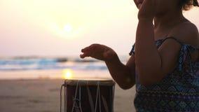 Милая девушка маленького ребенка играя барабанчики на песчаном пляже сток-видео