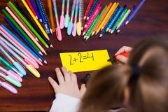 Милая девушка маленького ребенка пишет ` ` 2+2=4 текста Концепция образования детей стоковые изображения rf
