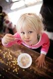 Милая девушка малыша есть хлопья для завтрака на солнечном утре стоковая фотография rf