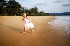 Милая девушка малыша со светлыми волосами в белом платье балетной пачки бежать на песчаном пляже на заходе солнца : стоковые фотографии rf