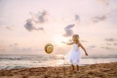 Милая девушка малыша со светлыми волосами в белых платье и шляпе балетной пачки идя на песчаный пляж на заходе солнца r стоковая фотография rf