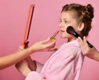 Милая девушка молодой дамы предназначенная для подростков с плюшками в салоне спа во время макияжа и прически оценивает ее выраже стоковые фото