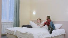 Милая девушка нарушает ее парня, пока он читал и пары начинают воевать с подушками Стоковое Изображение RF