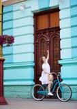 Милая девушка на ретро велосипеде против винтажной двери на лете Стоковые Изображения RF