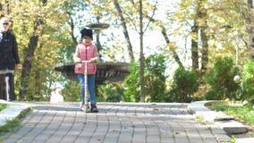 Милая девушка около 4 езд скутер вдоль путей в парке на красивый солнечный день осени День семьи сток-видео